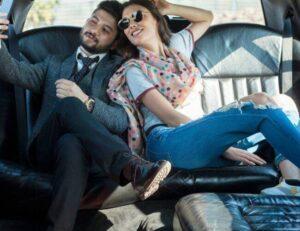Two friends on backseat in car taking selfie