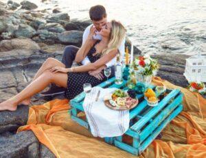 Happy romantic couple having picnic at beach