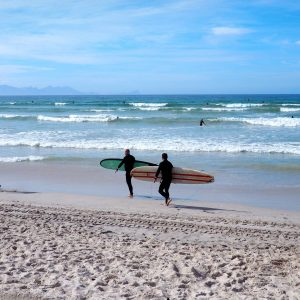 Two surfers walking on the beach in Cape Town
